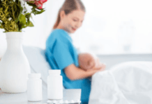 mother-breastfeeding-baby-in-hospital-bed-with-medication-on-side-table