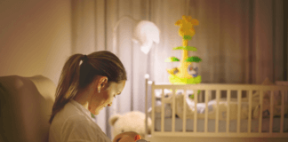 mother-breastfeeding-her-baby-in-lightly-lit-nursery-smiling-and-bonding-with-child