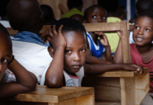preschooler-child-and-children-at-school-at-schooldesks-looking-at-the-camera