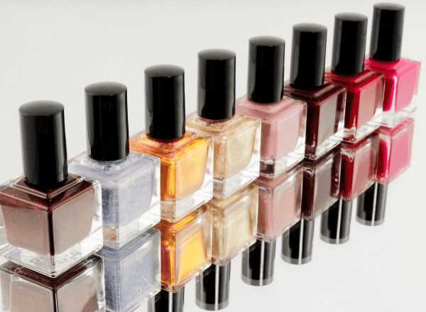 Bottles of coloured nail polish in a row