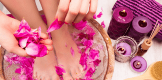 Feet soaking in a bowl of water while a woman does a DIY at-home pedicure