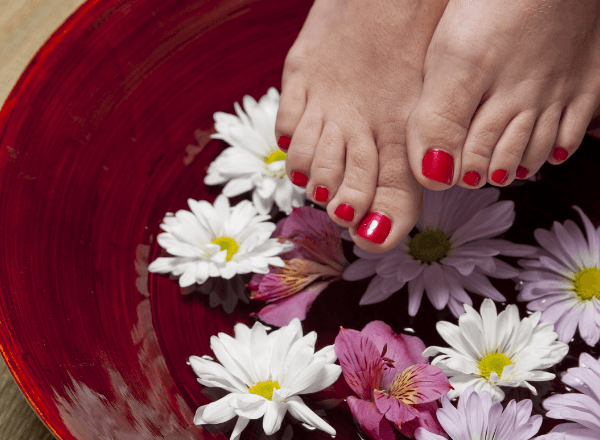 Red painted toenails over a bed of flowers floating on water