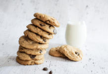 Stacked, chocolate and oat lactation cookies beside a glass of milk