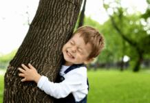 Nature loving child hugging a tree
