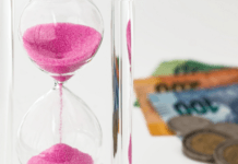 Pink sand hourglass next to rands currency