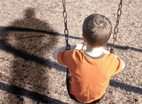 small-boy-playing-on-a-swing-with-child-abductor-standing-behind-him