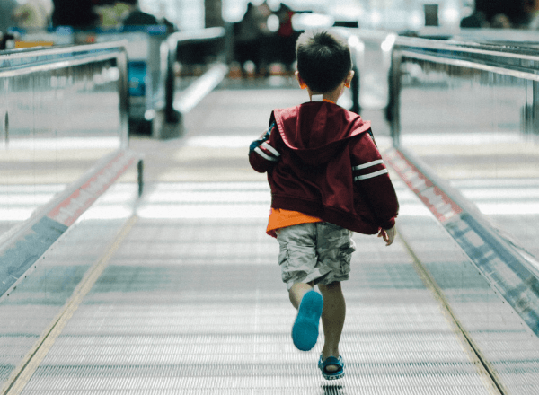 small-toddler-running-on-ramp-in-airport-while-travelling-on-holiday-with-family