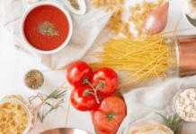 Uncooked spaghetti pasta with tomatoes on table