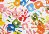 Children's hand prints in different paint colours