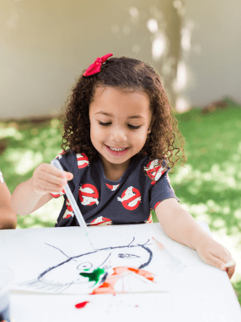 Happy child painting scary monster