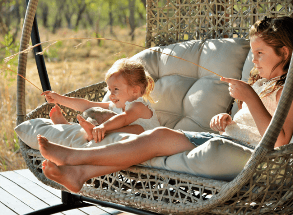Children on wicker swing at game lodge