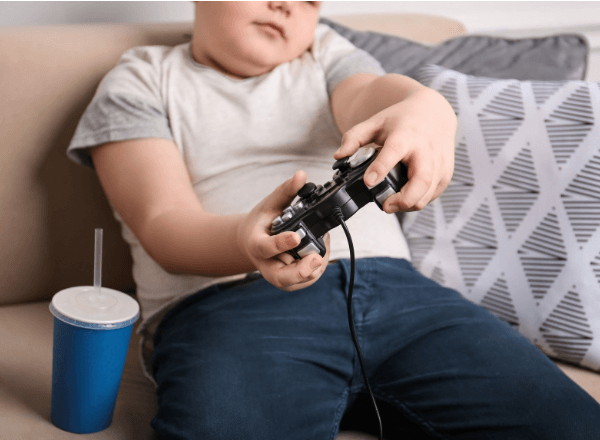 Obese child playing video games on couch