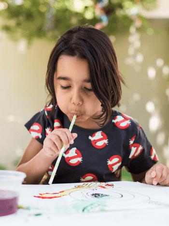 Preschooler blowing paint through a straw