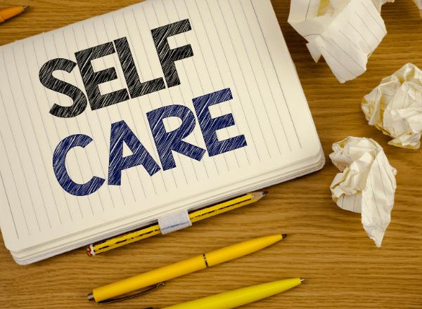 Self care written on notepad in pen