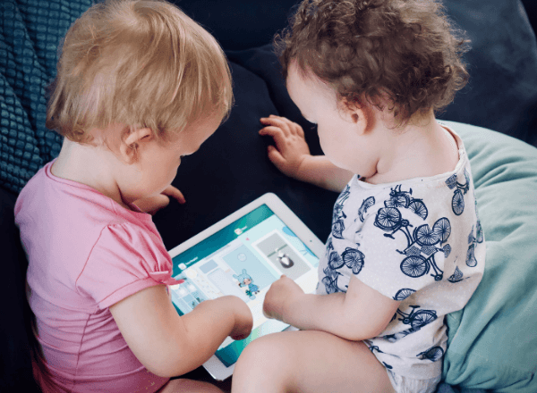 Two toddlers playing on a tablet screen