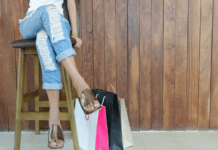 Lady sitting on stool with shopping bags at feet