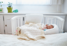 Newborn baby in cot next to mother's bed