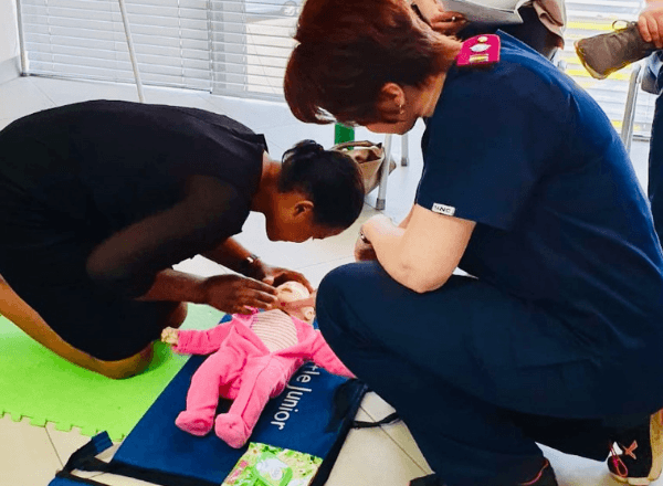 Nurse showing mother how to perform CPR