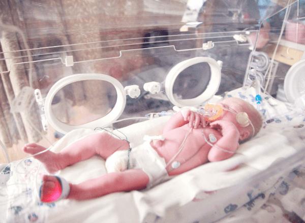Premature newborn baby in ICU incubator