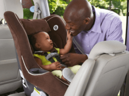 Baby in car seat being safely strapped in
