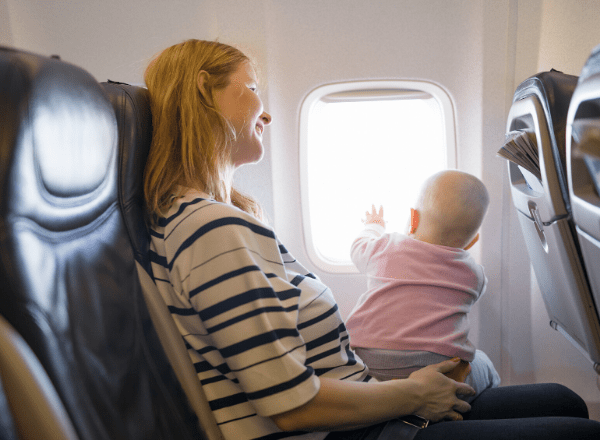 Smiling mom in aeroplane with baby on lap