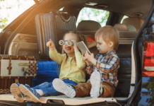Toddlers playing in boost of car waiting for a road trip