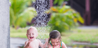 Toddlers playing outside under the sprinkler