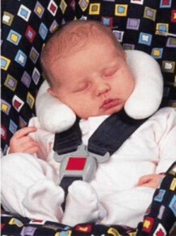 Baby wearing neck pillow in car seat