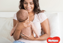 Smiling mom holding baby in Huggies nappy