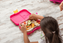 Preschooler girl opening her healthy lunchbox