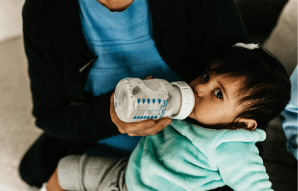 Toddler child being formula fed with bottle