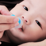Small baby being given medicine orally