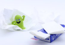 Smiling green germ next to pile of tissues