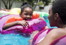 Smiling toddler swimming with armbands in pool