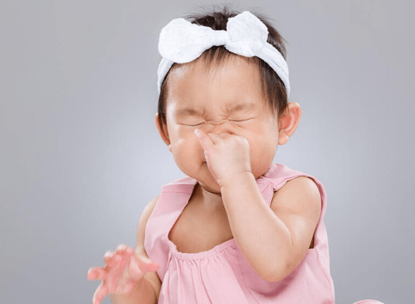 Chinese baby holding nose while sneezing