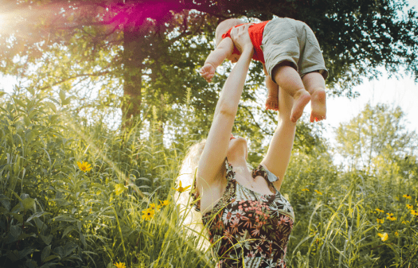 Happy mom lifting son in green field
