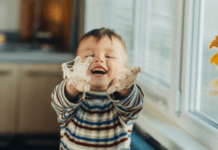 Happy toddler reaching out with goopy hands