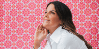 Lou Harvey smiling with pink background
