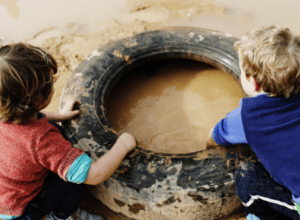 Preschoolers playing with messy mud in tyre