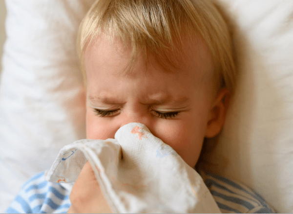 Sick boy preschooler holding handkerchief to nose