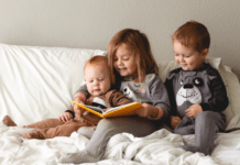 Three children on bed reading a book