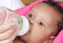 Baby girl drinking bottle of formula milk