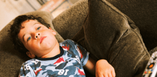 Bored preschooler boy lazing on brown couch