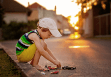Boy playing with toy cars in street