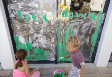 Brother and sister painting on glass doors