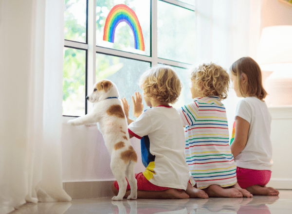 Two children and dog looking outside window