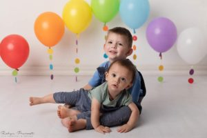 Photo of happy brothers with colourful balloons