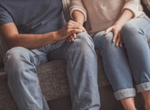 Anxious couple sitting on couch holding hands