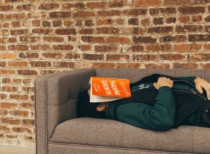Man asleep on couch with book on face