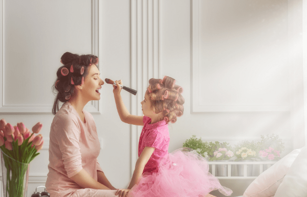 Little girl having make-up session with mom